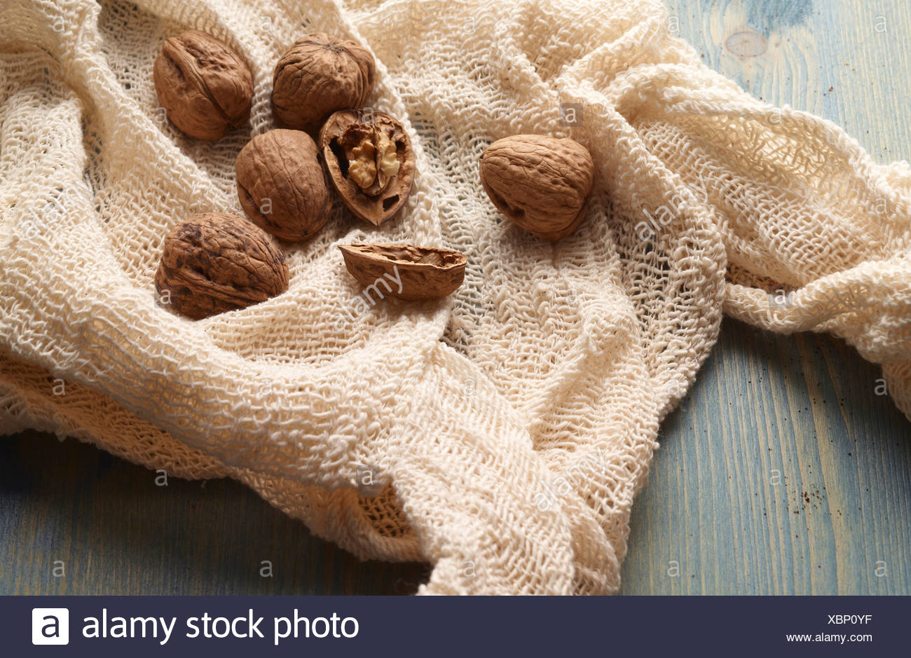 Walnuts in knitted fabric on table - Stock Image