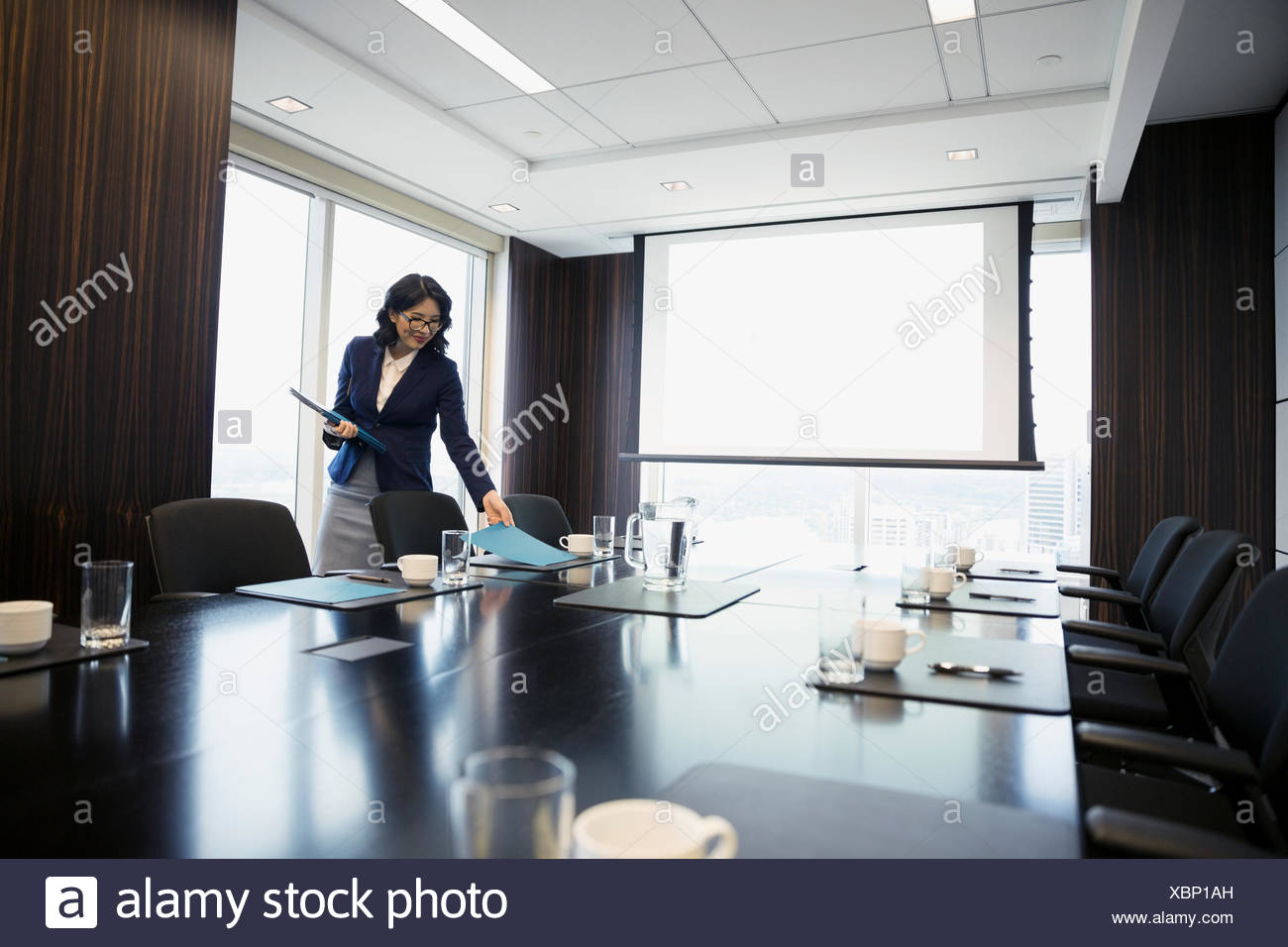 Businesswoman preparing for meeting placing folders on conference room table - Stock Image