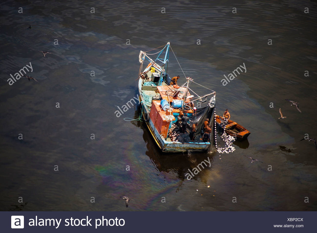 Small fishing boat at the polluted waters of Guanabara Bay, Rio de Janeiro, Brazil. Oil spill near Paqueta island. - Stock Image
