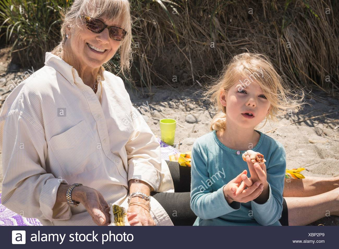 Grandmother and granddaughter on beach with picnic - Stock Image