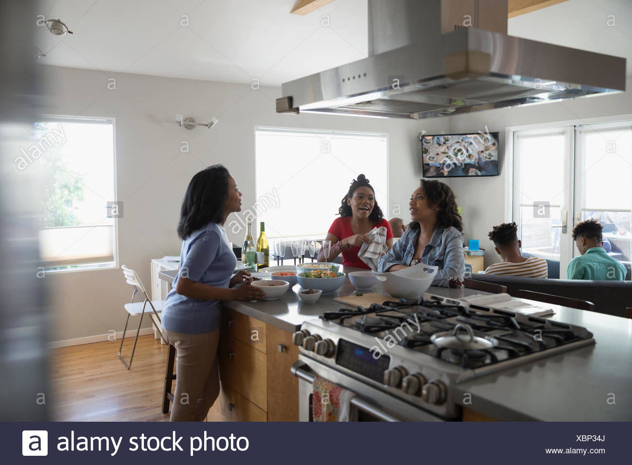 African American mother and teenage daughters cooking and eating in kitchen Stock Photo