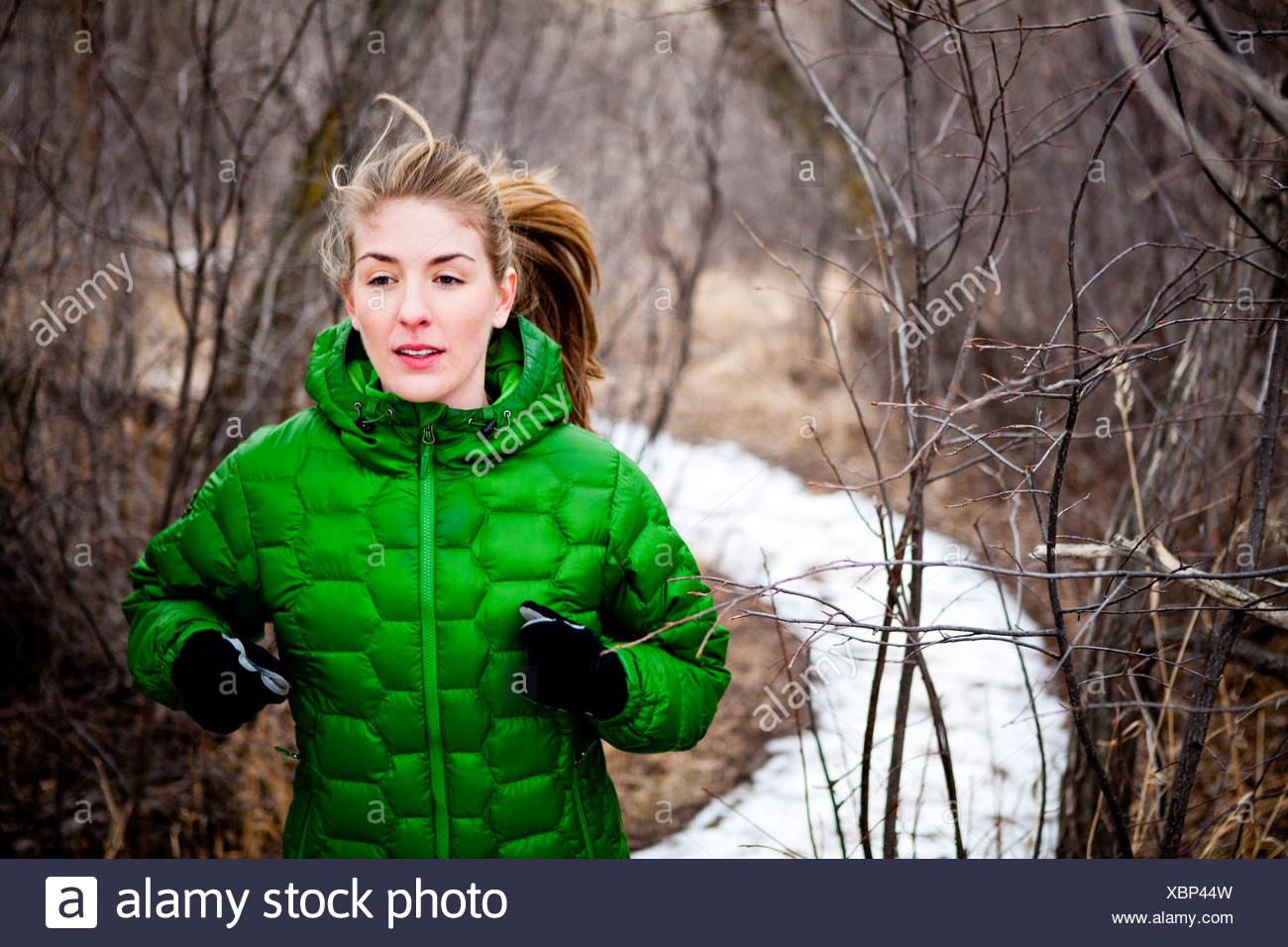 a young woman runs a along snow covered dirt trail through leafless deciduous trees just north of Dixon Reservoir, on a cold day - Stock Image