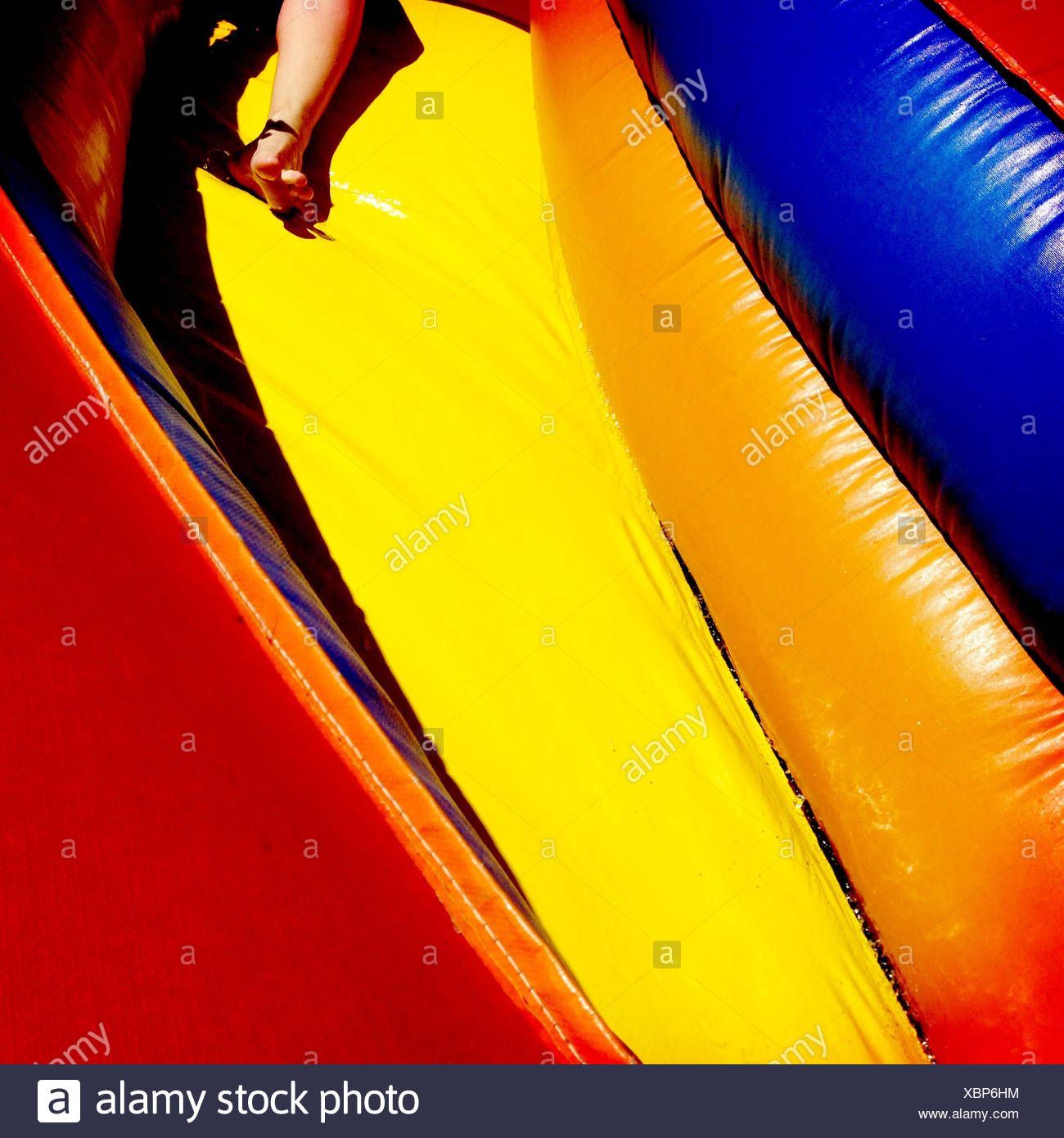 legs of person sliding down colorful waterside - Stock Image