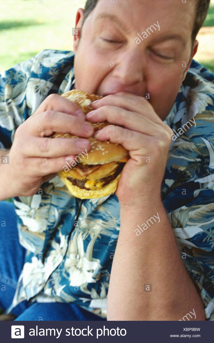 Overweight man eating hamburger - Stock Image