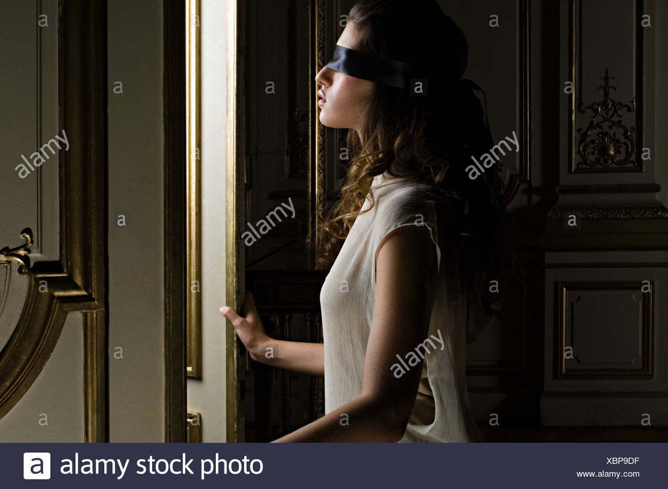 Blindfolded woman opening door Stock Photo