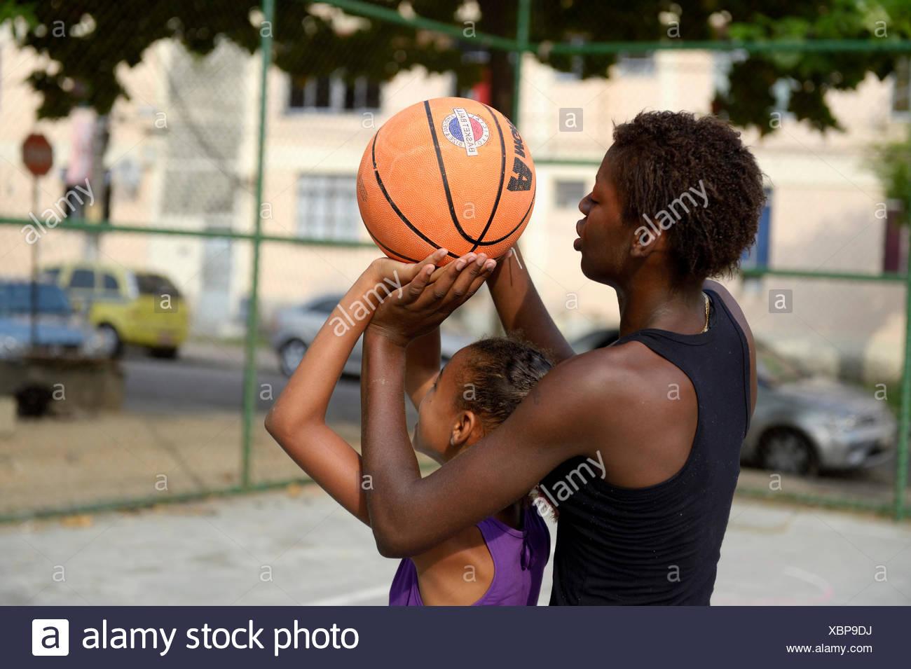 Two girls, 15 and 10, training basketball, Rio de Janeiro, Rio de Janeiro State, Brazil Stock Photo