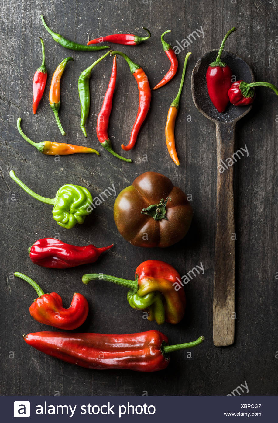 Red and green vegetables and rustic old spoon on dark wooden background, top view. Peppers, chilis and kumato tomatoes - Stock Image