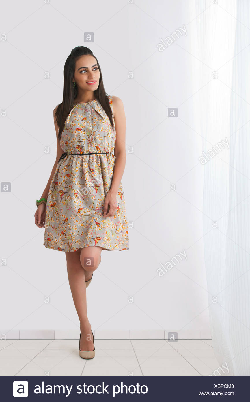 Full length of beautiful young woman in sundress leaning against wall - Stock Image
