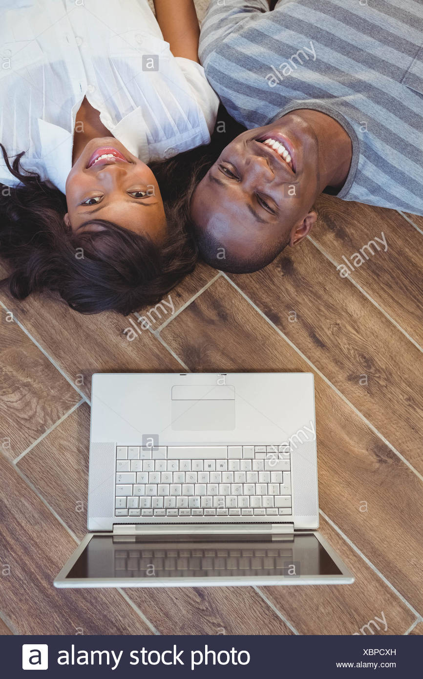 Ethnic couple lying on the floor - Stock Image
