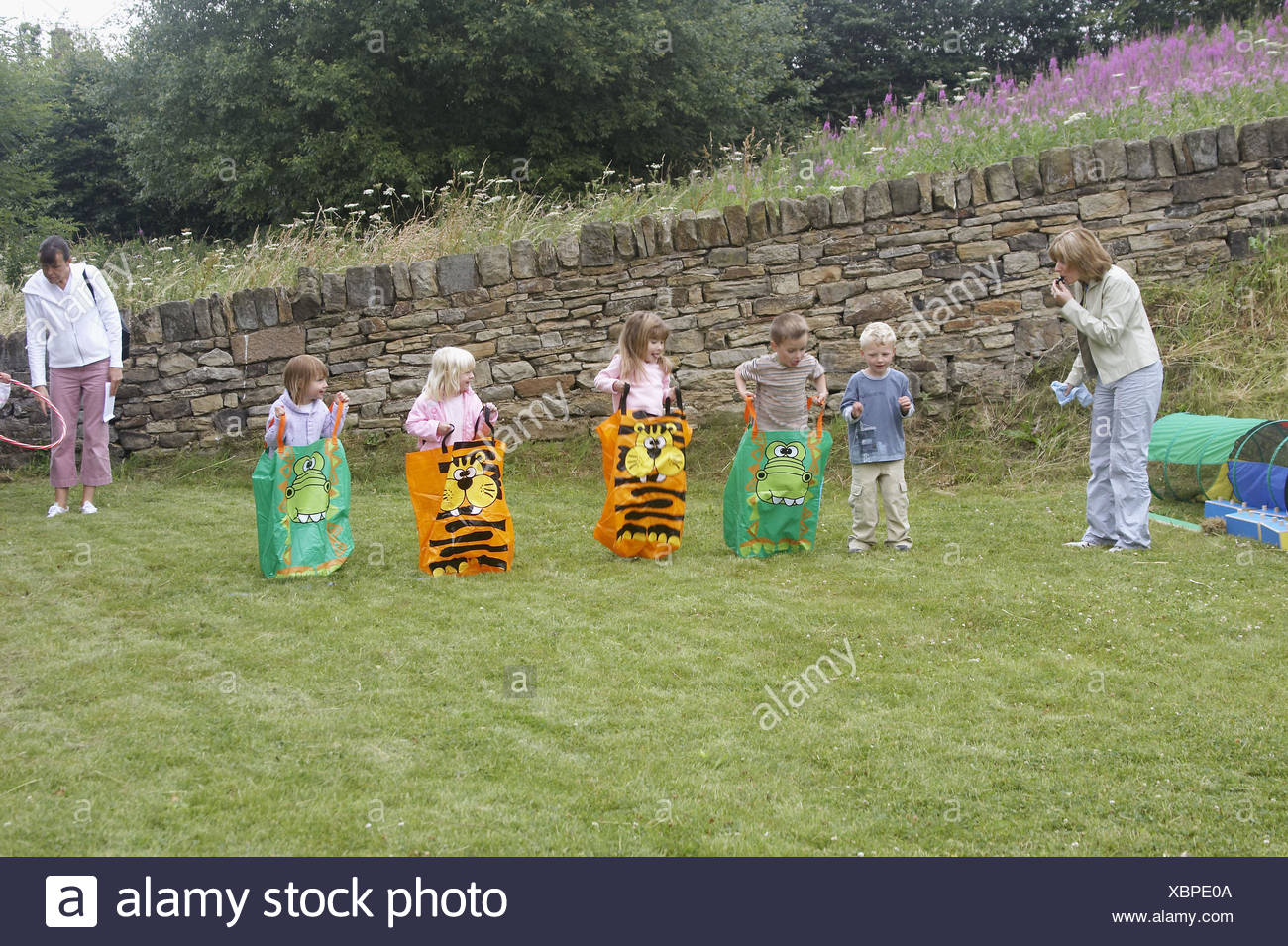 Group of pre school children doing a sack race on sports day - Stock Image
