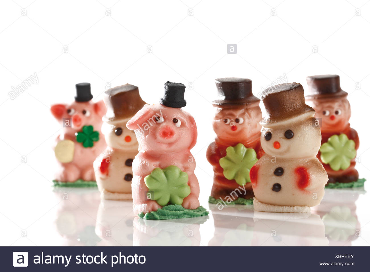 Lucky charms made of marzipan, pigs, snowmen, chimney sweeper - Stock Image