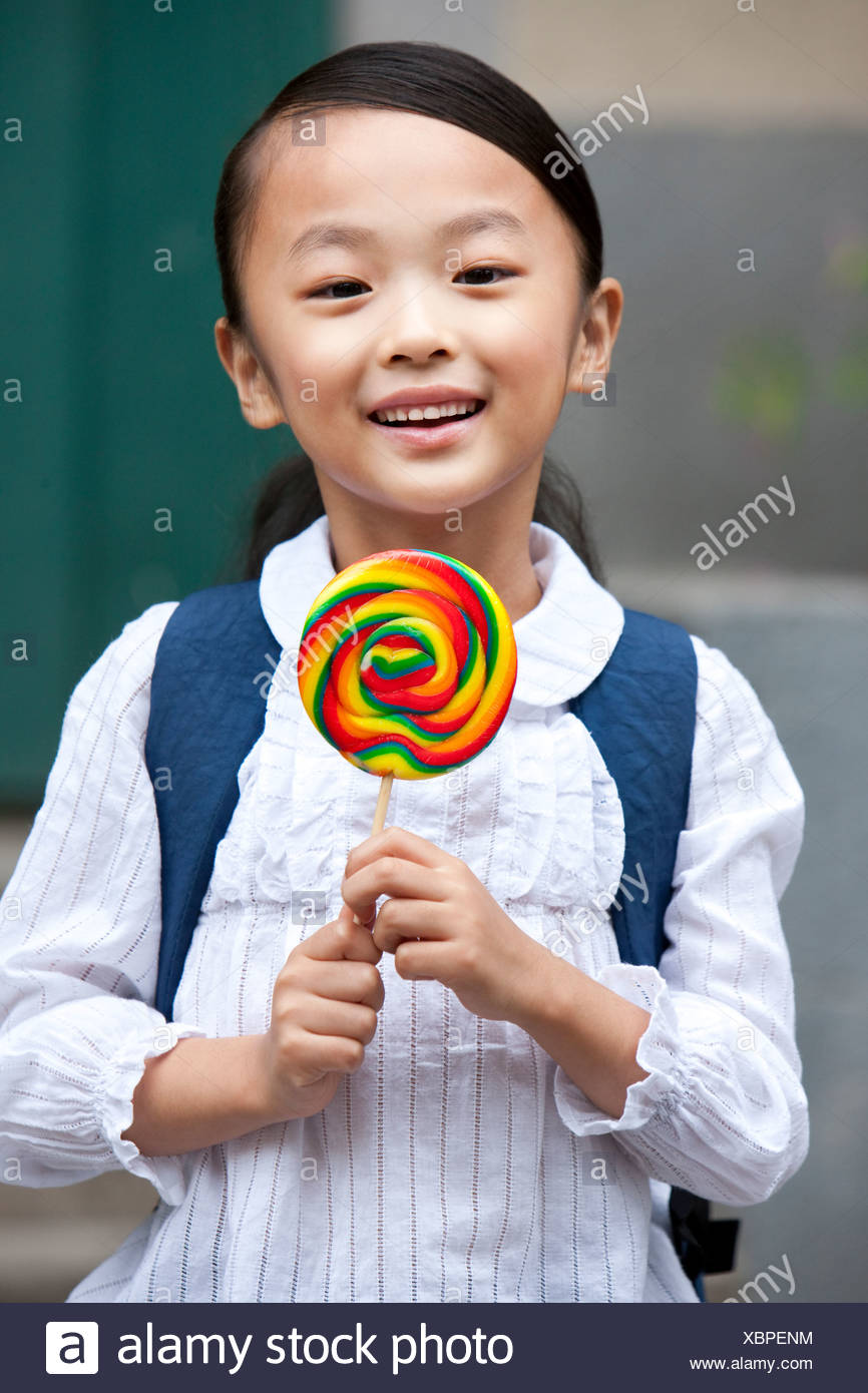 A happy girl with a lollipop - Stock Image