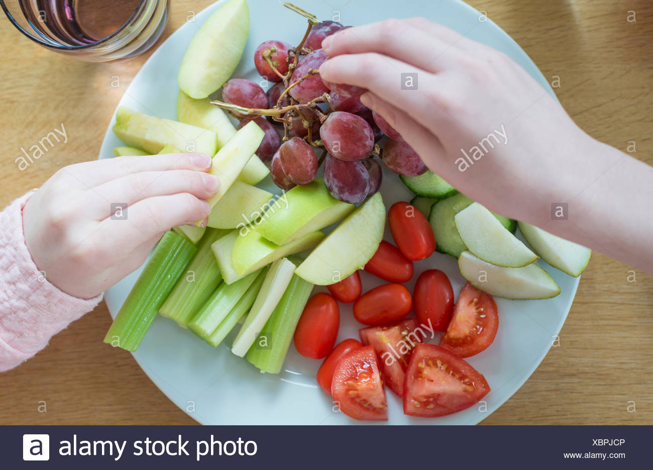 Hands taking fruit from a plate of snack food. - Stock Image