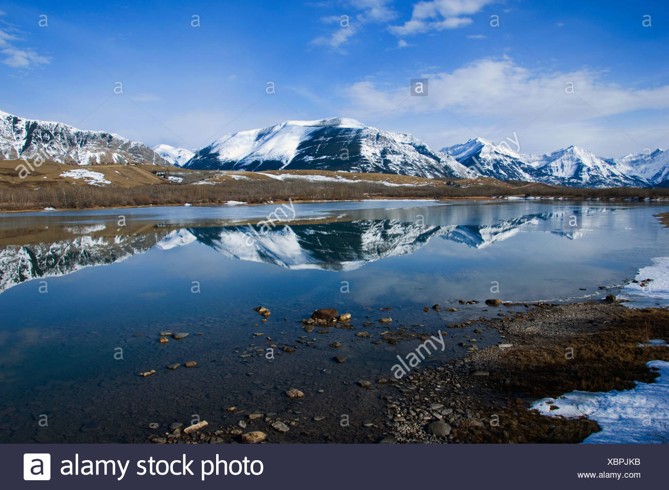 Reflection of area Mountains. Until the snowpac begins to melt the water level is down exposing gravel along the edges. As tempe - Stock Image