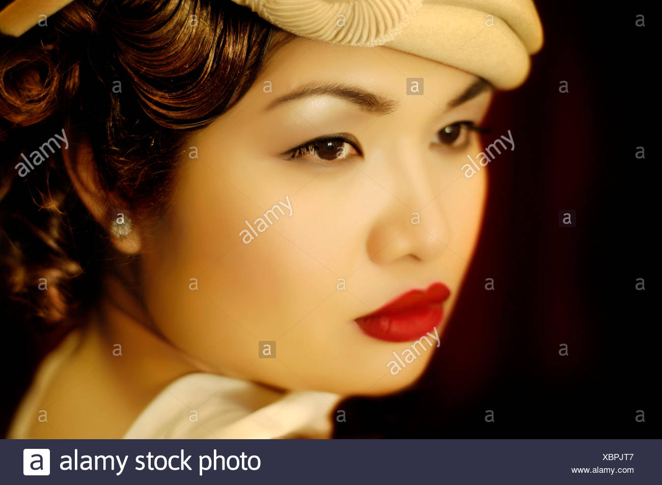 An Asian woman in her early twenties dressed in early 1940's attire, looks over her left shoulder. Her make-up is elegant and her lipstick is bright red. - Stock Image
