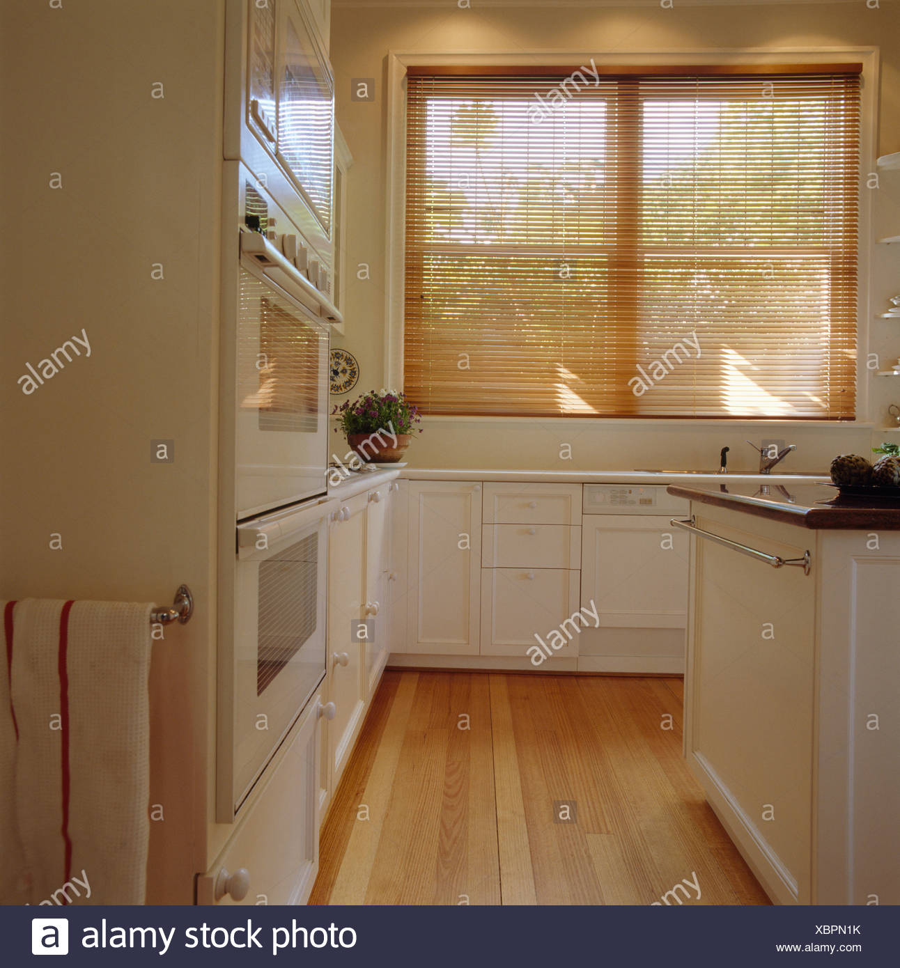 Slatted Wooden Blind And Wooden Flooring In Modern White Kitchen Stock Photo Alamy