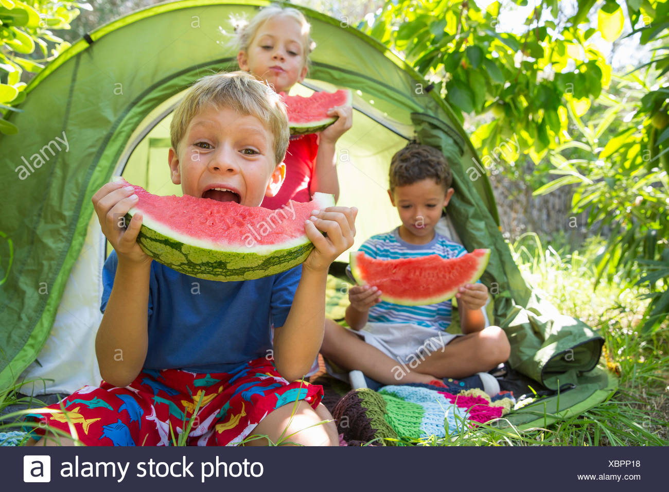 Three children eating large watermelon slices in garden tent - Stock Image