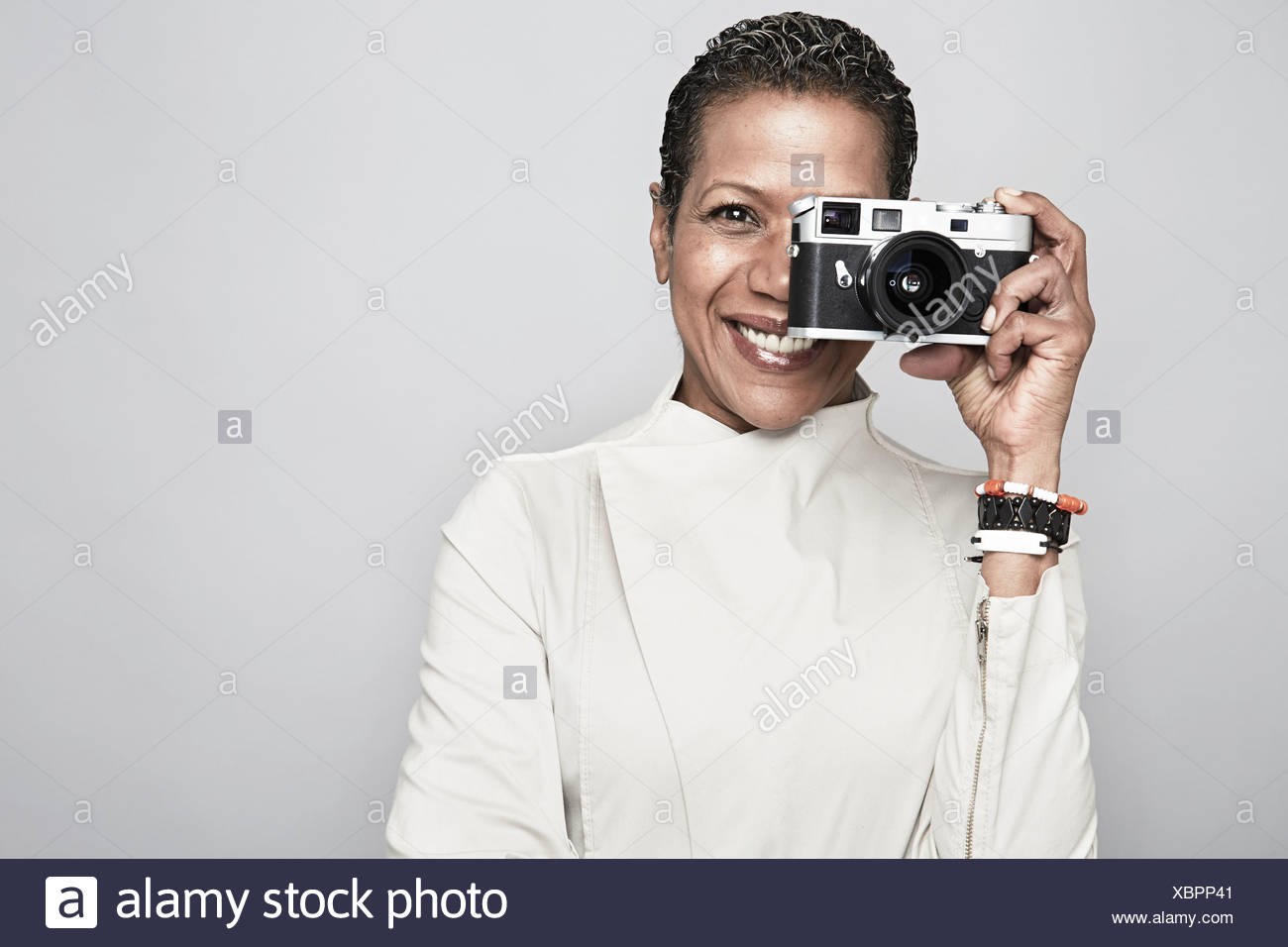 Studio portrait of happy mature woman holding up camera Stock Photo