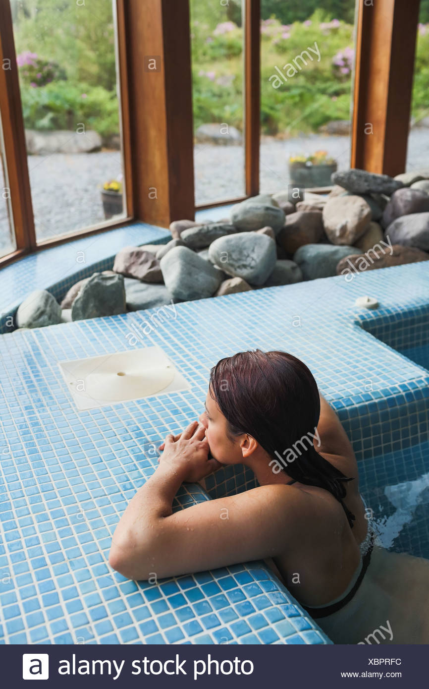 Brunette relaxing in a jacuzzi - Stock Image