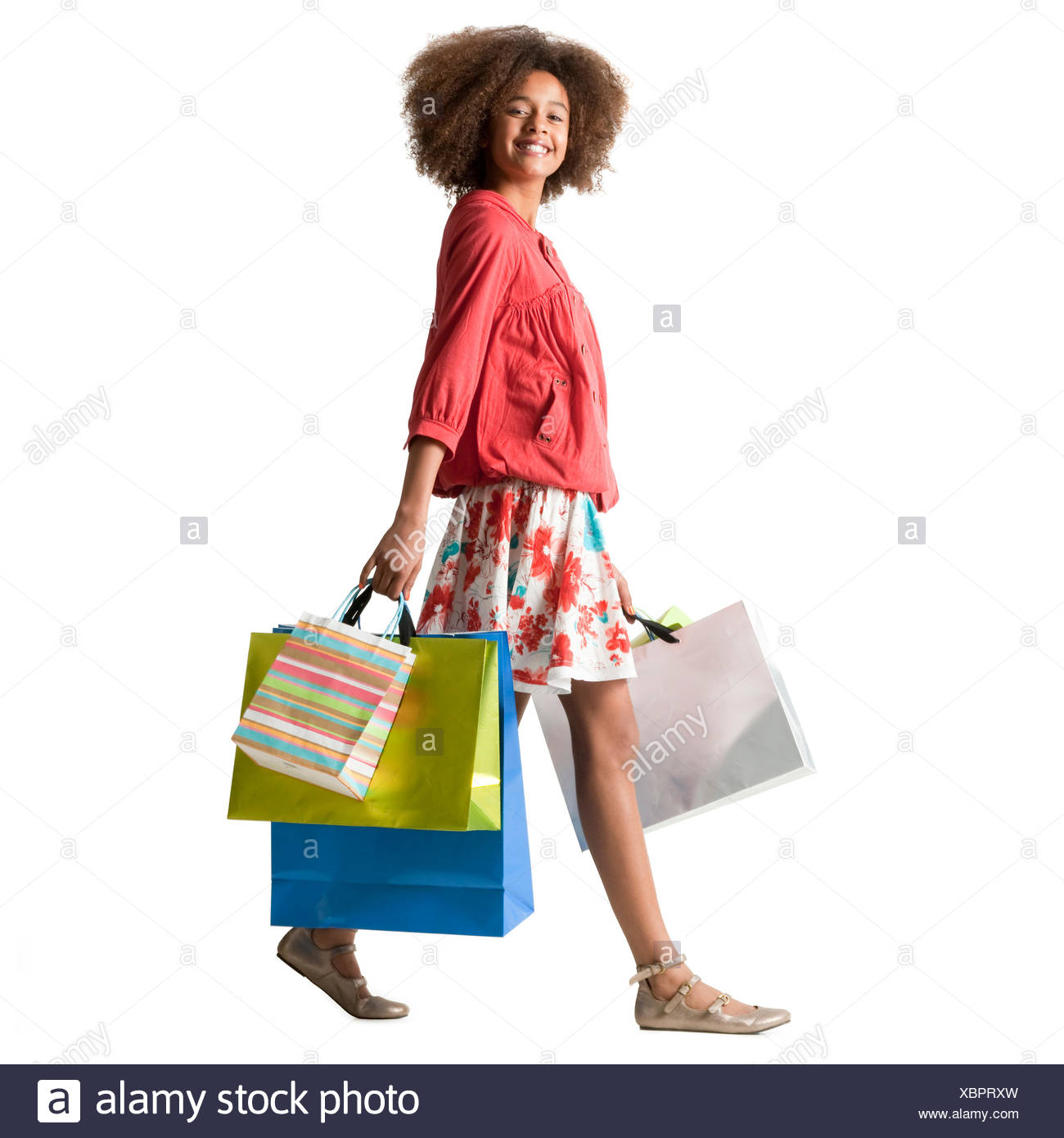 Teenage girl (12-13) carrying multi colored shopping bags,studio shot - Stock Image
