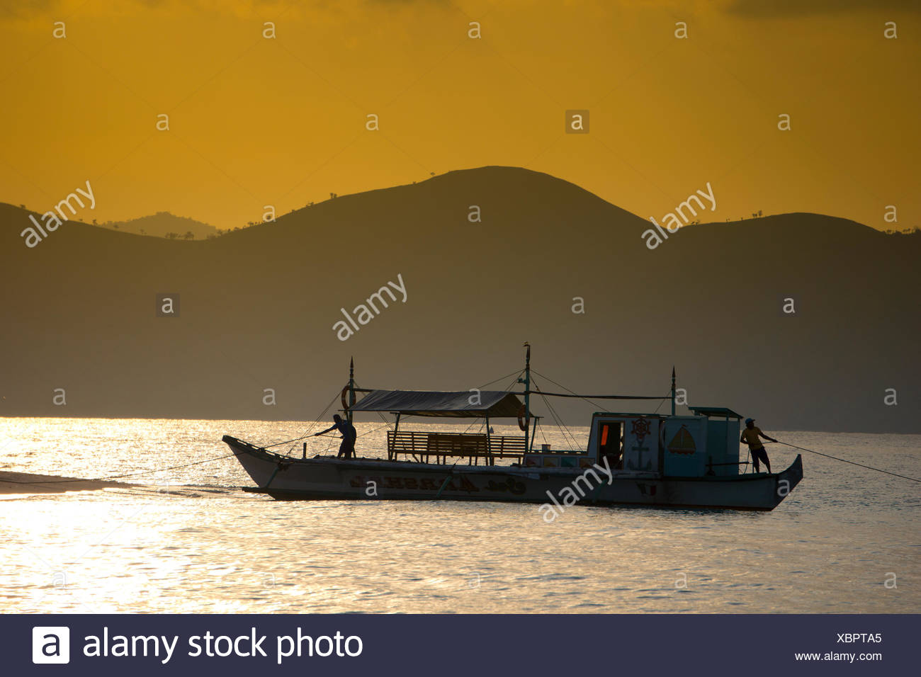 Banka, a traditional Filipino outrigger boat, anchored off the beach in the evening light, Busuanga, Philippines, Asia - Stock Image