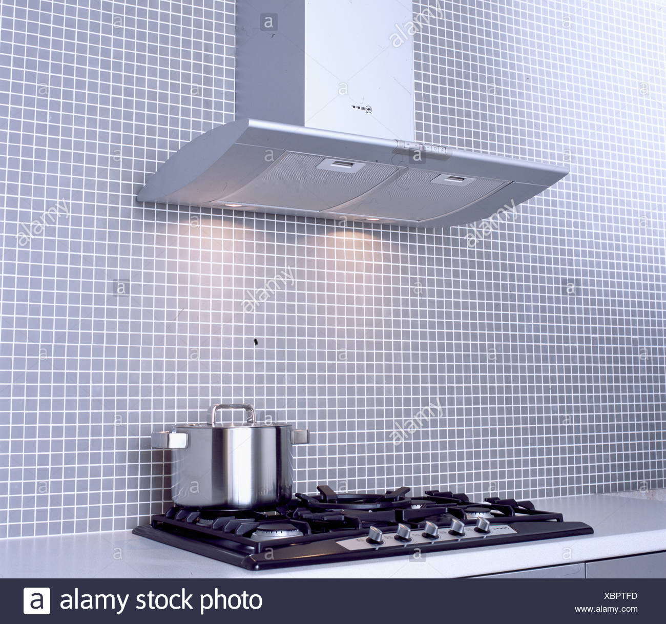 Close Up Of Extractor Fan Above Stainless Steel Pan On Black Hob In Modern Kitchen With Mosaic Tiled Wall Stock Photo Alamy
