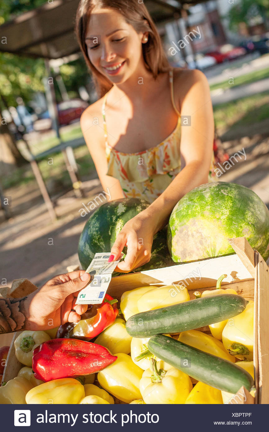 Woman buying vegetables at market stall - Stock Image