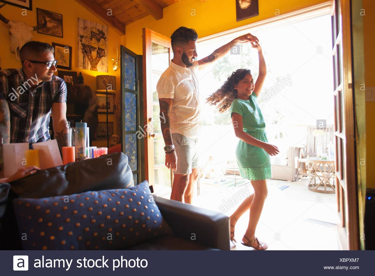 Girl dancing and twirling with father in living room - Stock Image