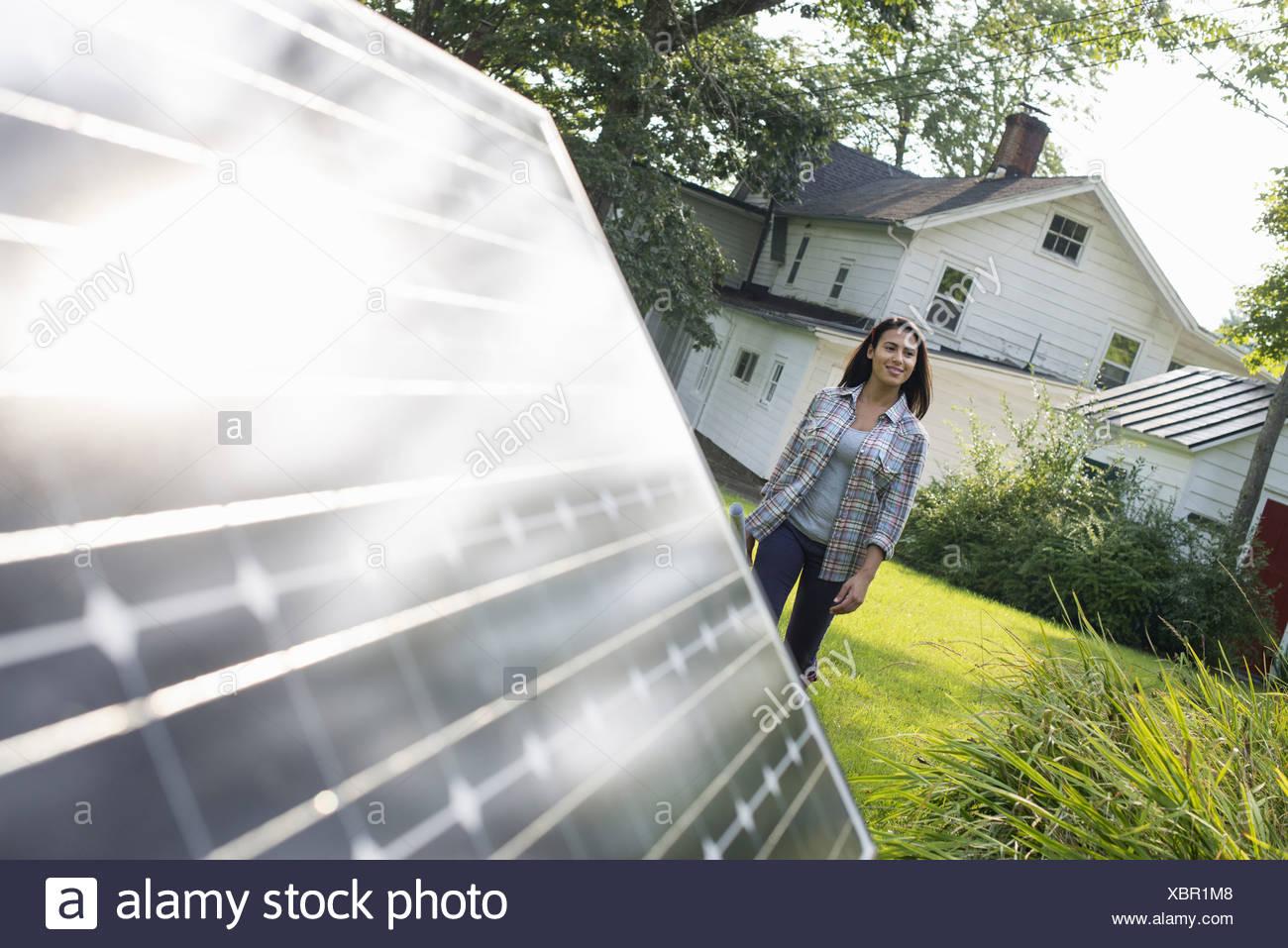 A woman walking towards a solar panel in a farmhouse garden. - Stock Image
