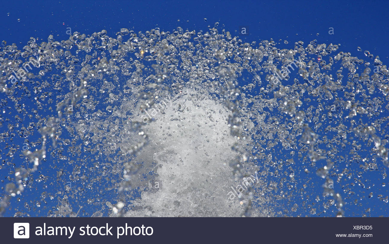 Fountain drops of pure water against a blue sky. - Stock Image