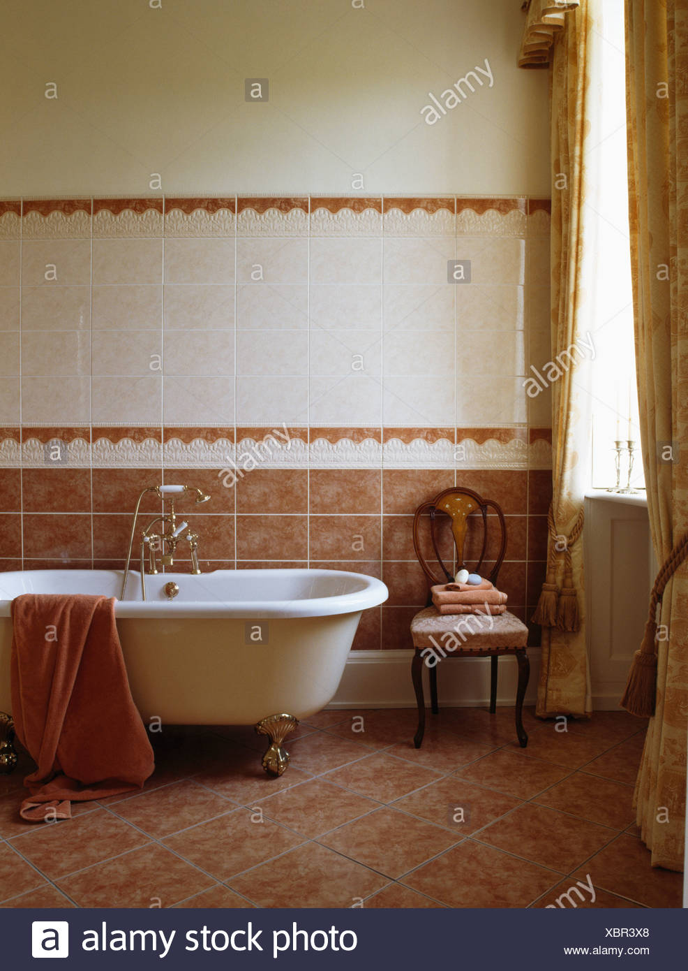 Roll-top bath in terracotta and white tiled bathroom with