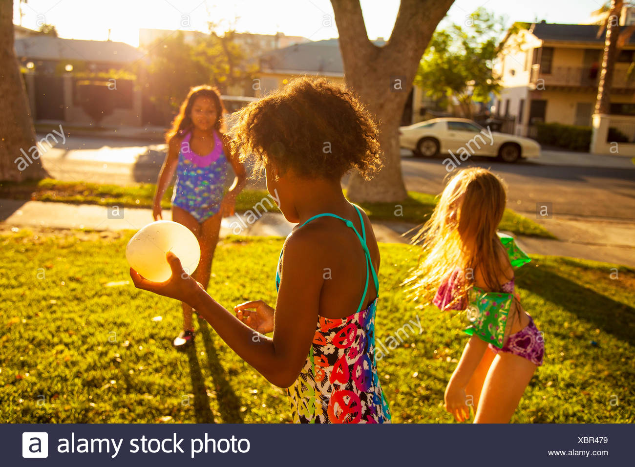 Three girls playing with water balloons in garden - Stock Image
