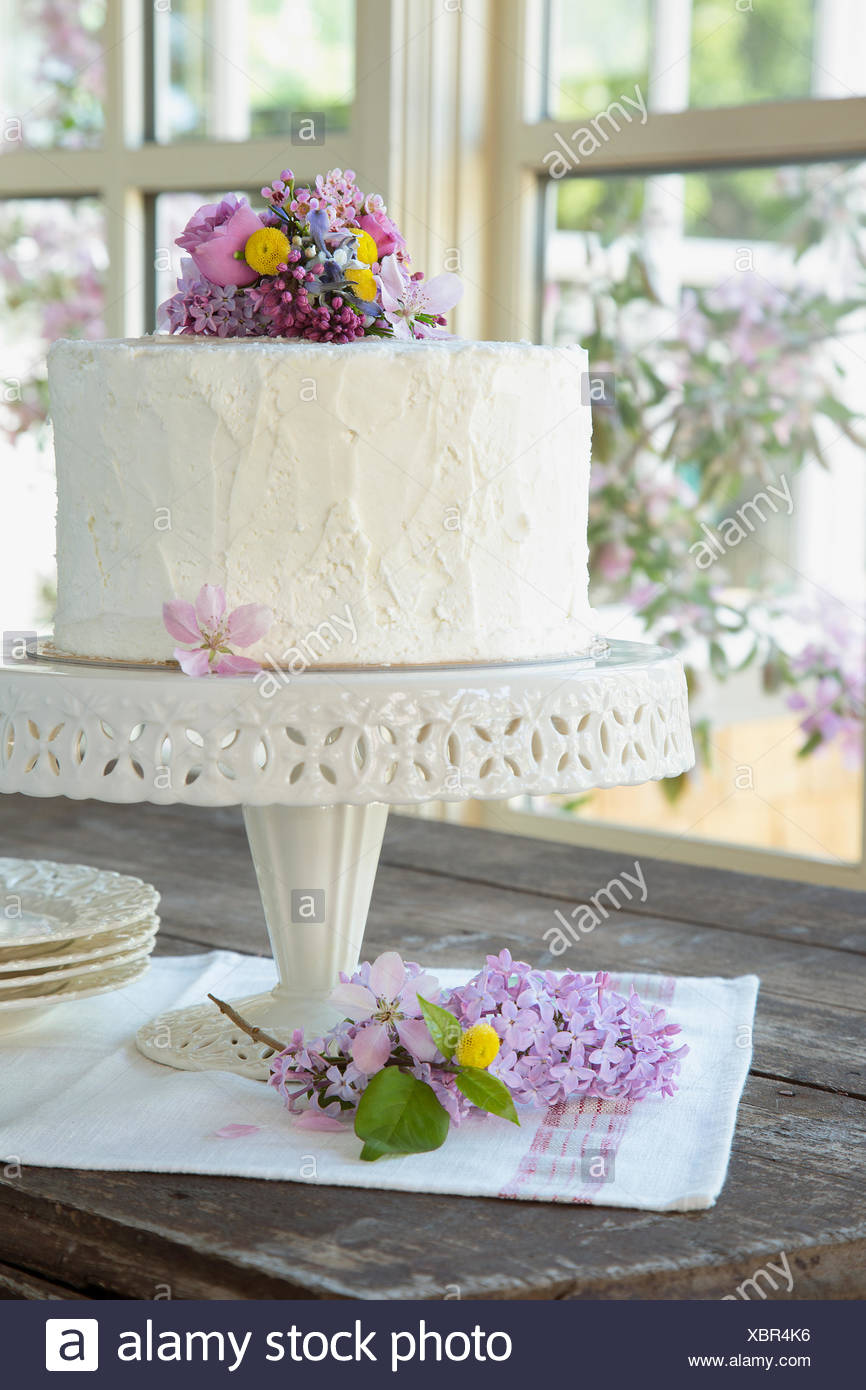 Spring flowers on white birthday cake - Stock Image