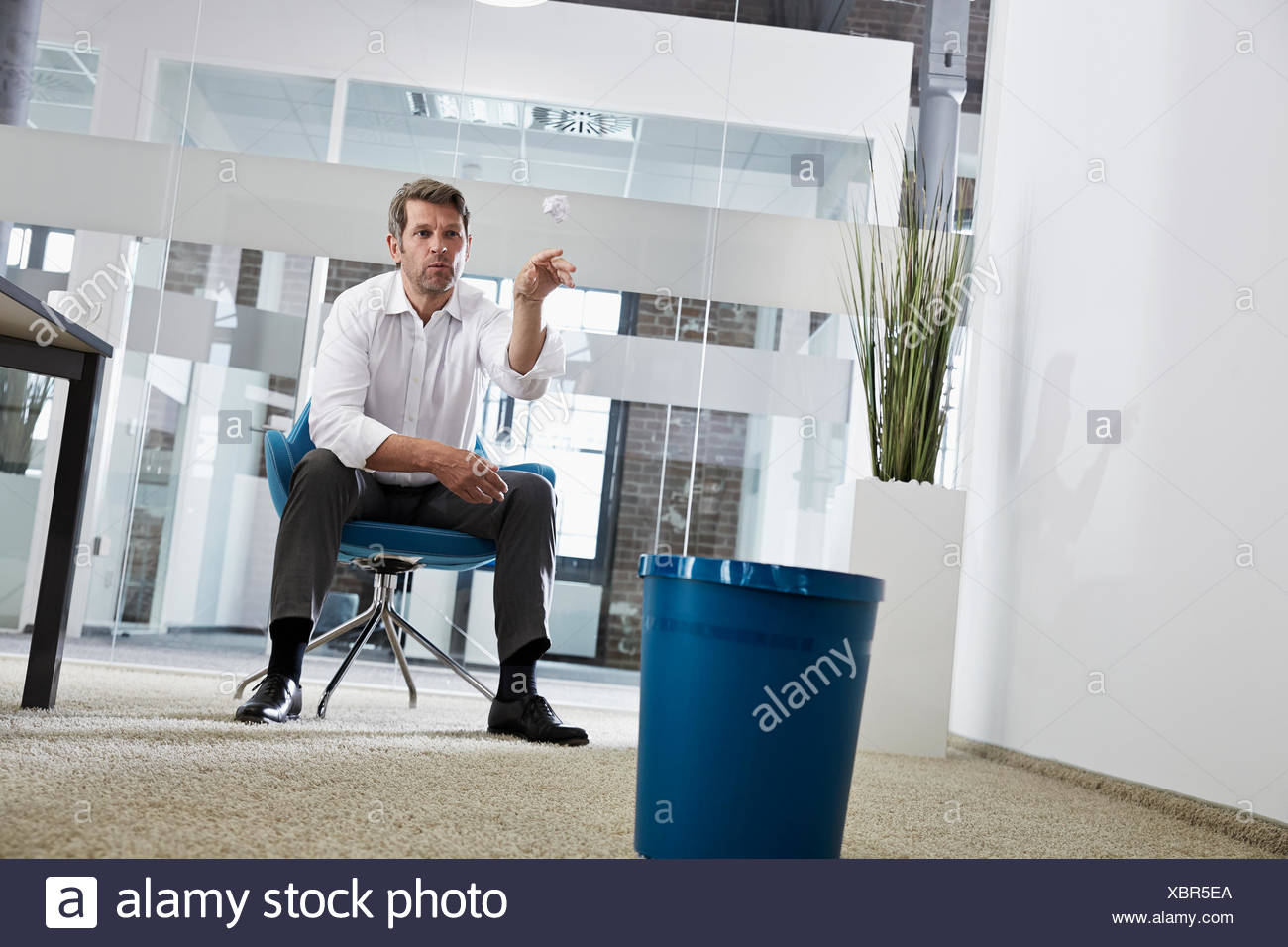 Businessman in office throwing crumpled paper in wastepaper basket Stock Photo