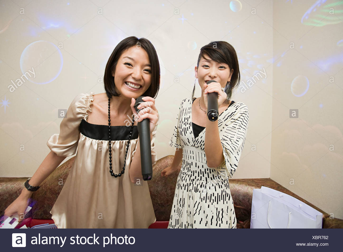 Friends singing karaoke - Stock Image