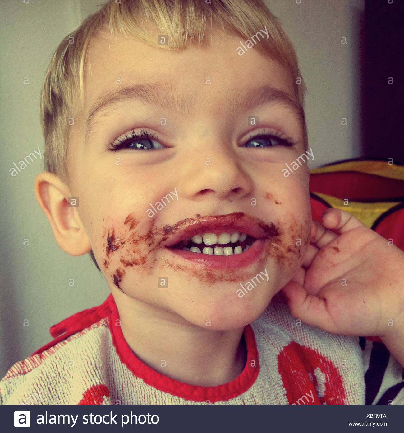 Portrait Of Cute Boy After Eating Chocolate Cake At Home - Stock Image