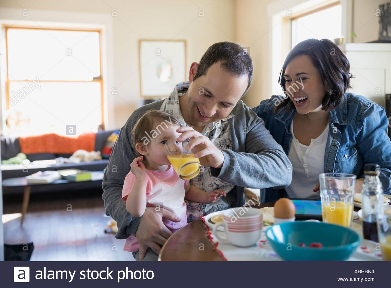 Young family enjoying breakfast at dining table - Stock Image
