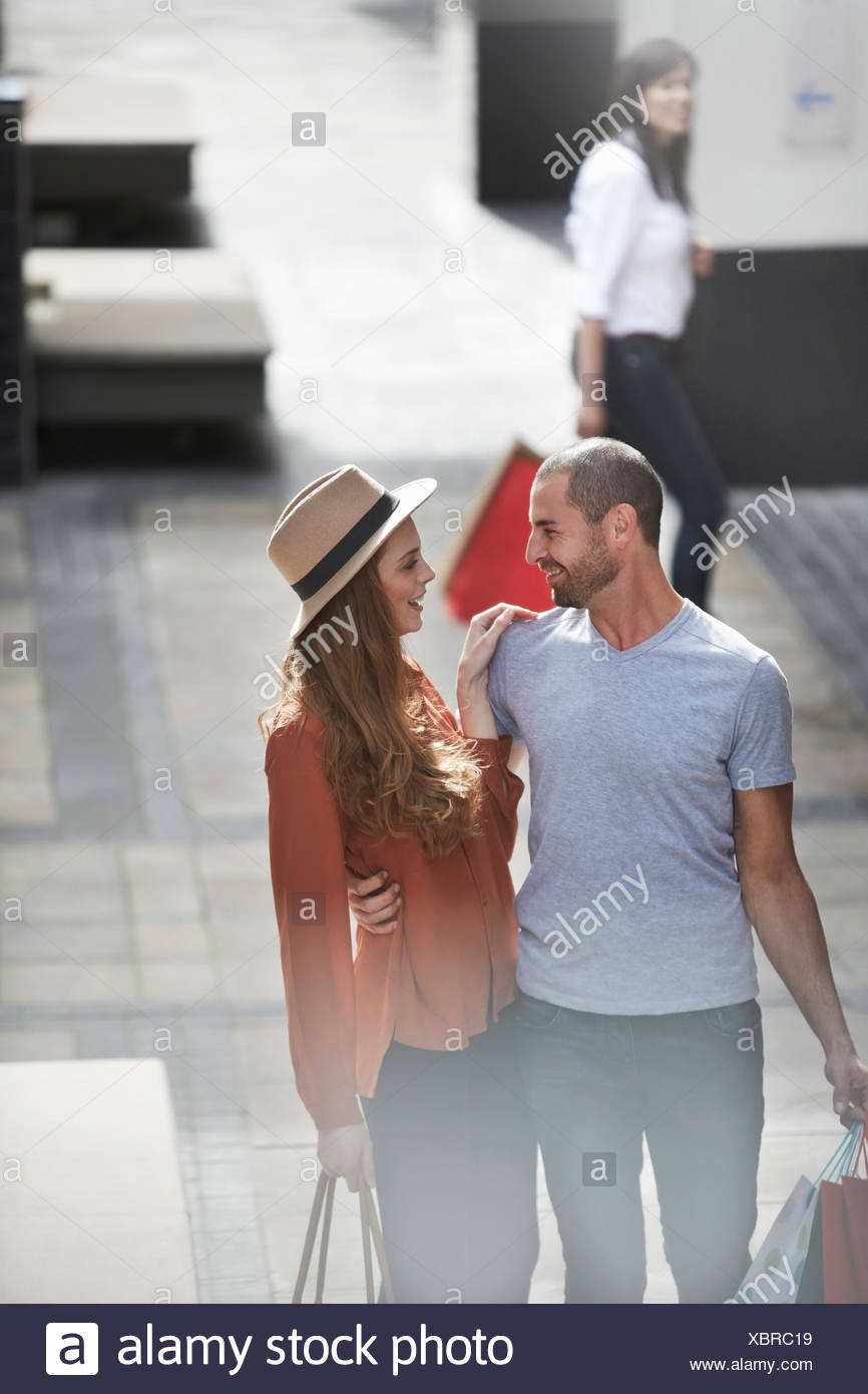 Couple in shopping mall, standing face to face, holding shopping bags - Stock Image