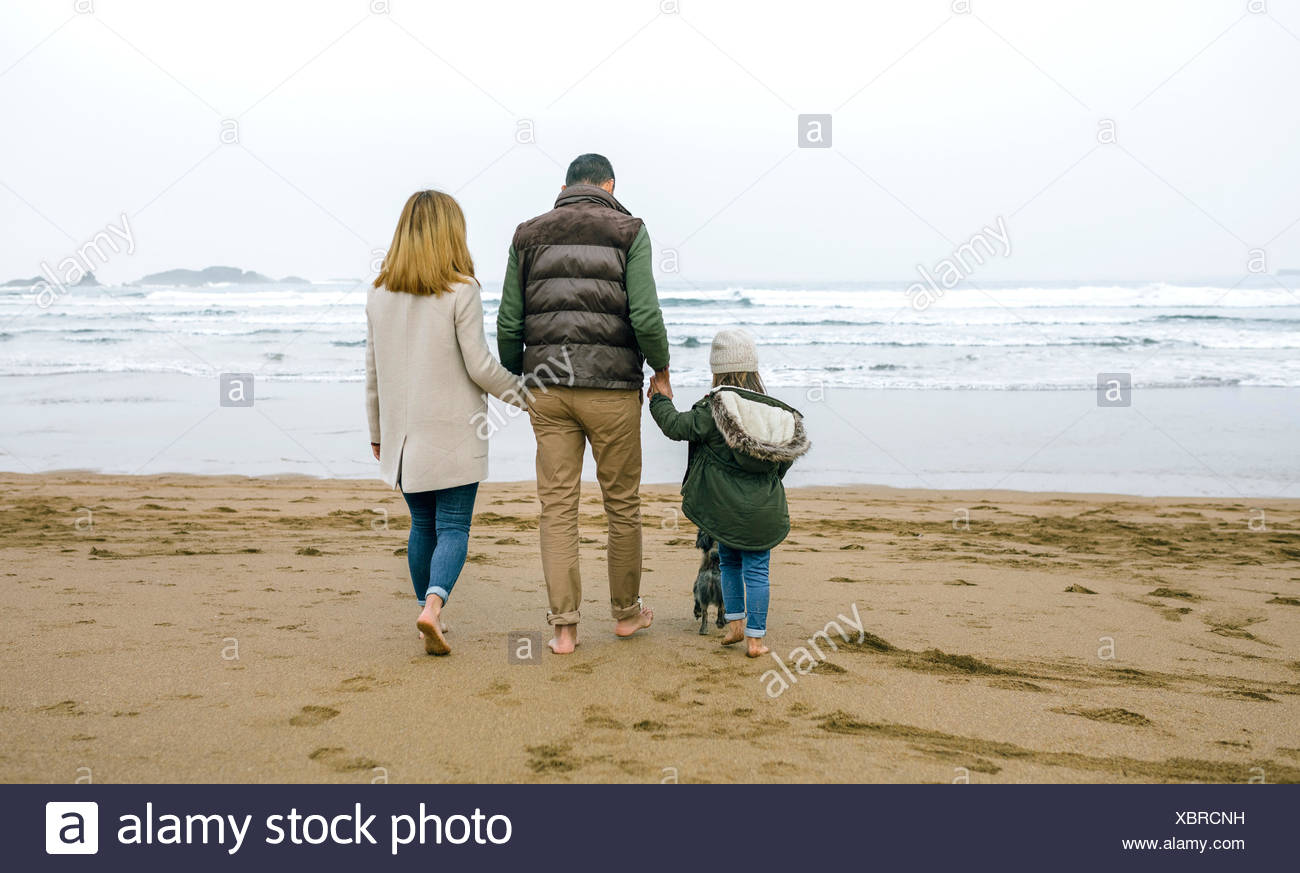Family walking with dog on the beach in winter - Stock Image