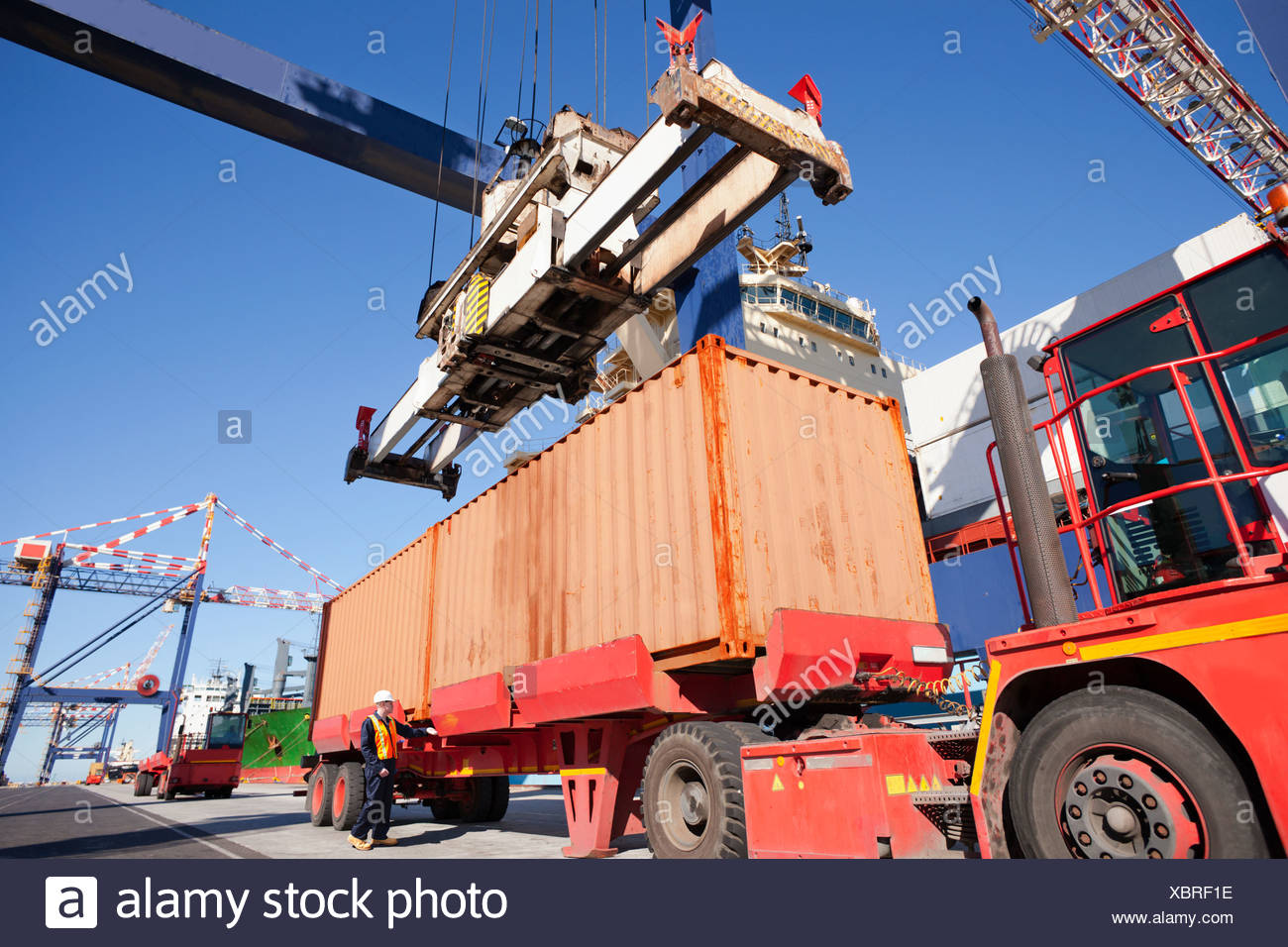 Crane unloading cargo container onto lorry at commercial dock - Stock Image