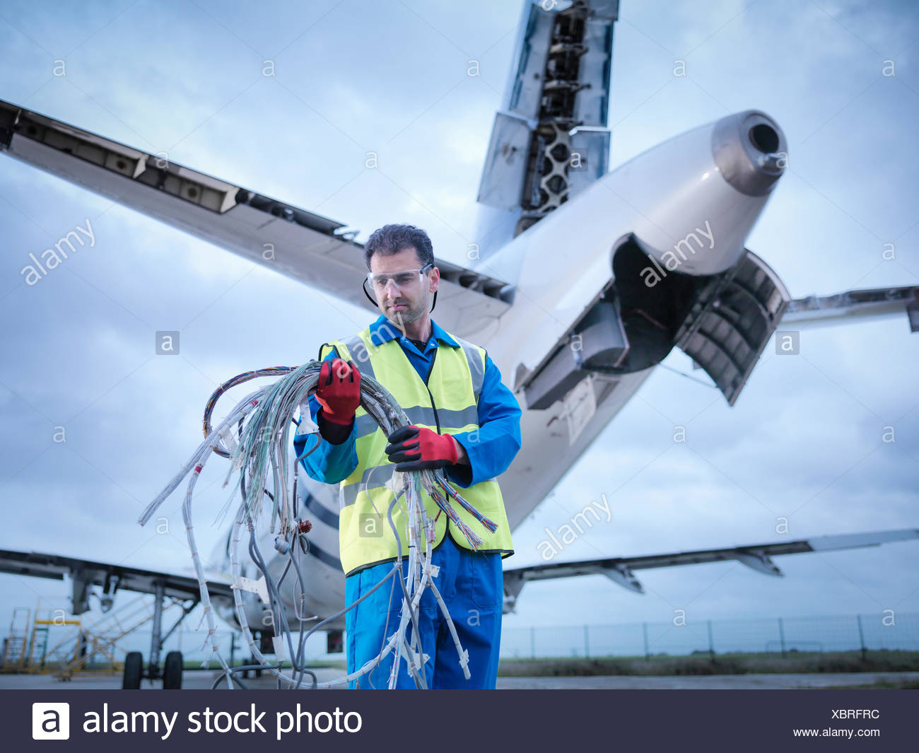 Engineer recycling aircraft parts on runway - Stock Image