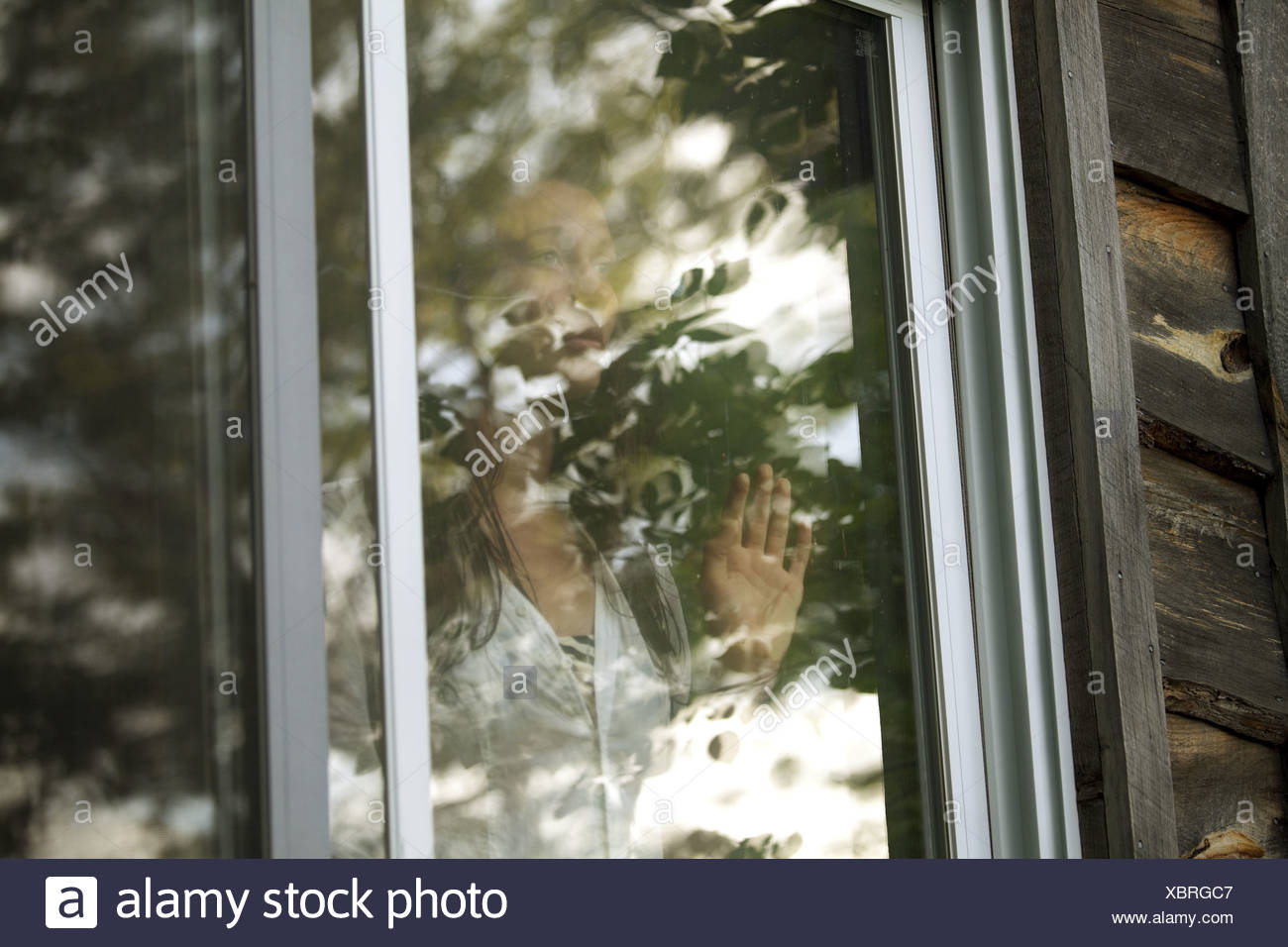 Teenage girl looking through window - Stock Image