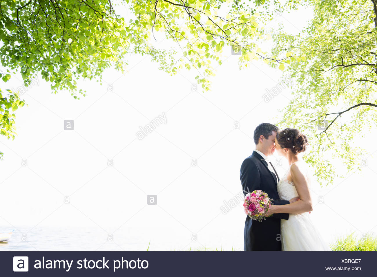Romantic newlywed mid adult couple kissing in park Stock Photo