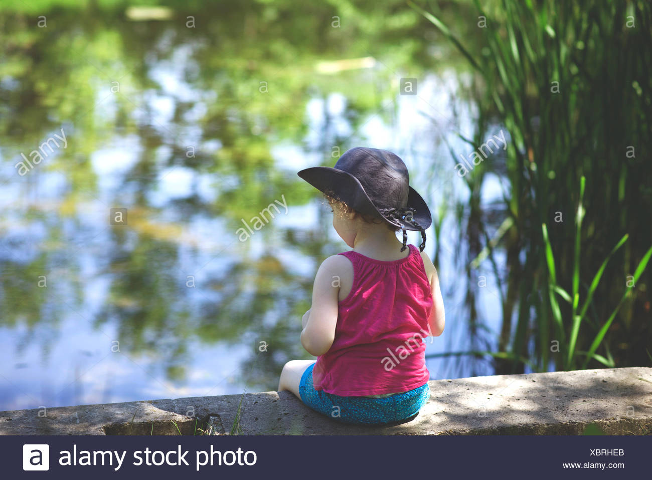 Girl (4-5) sitting by pond - Stock Image