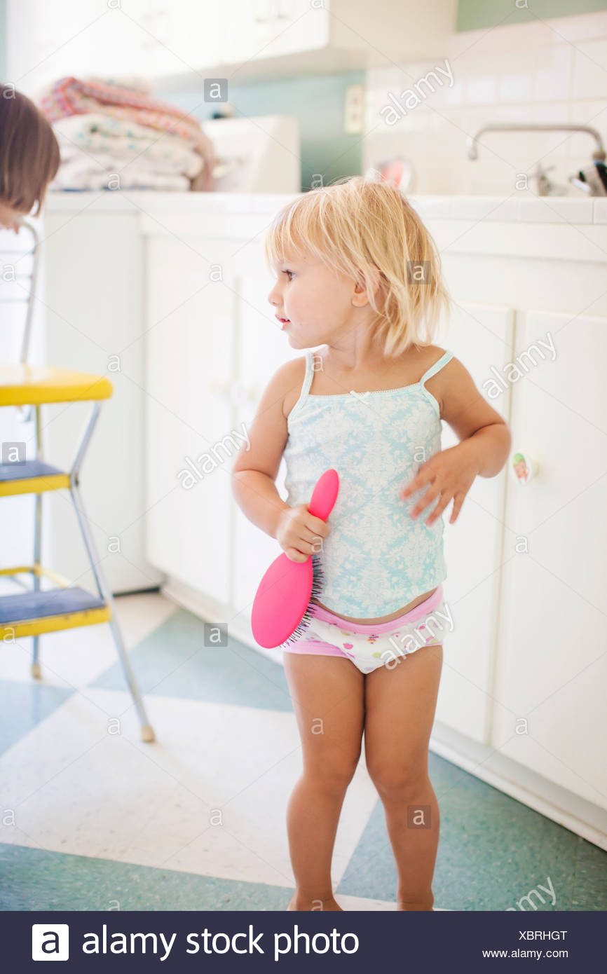 Girl wearing vest and knickers holding hairbrush - Stock Image