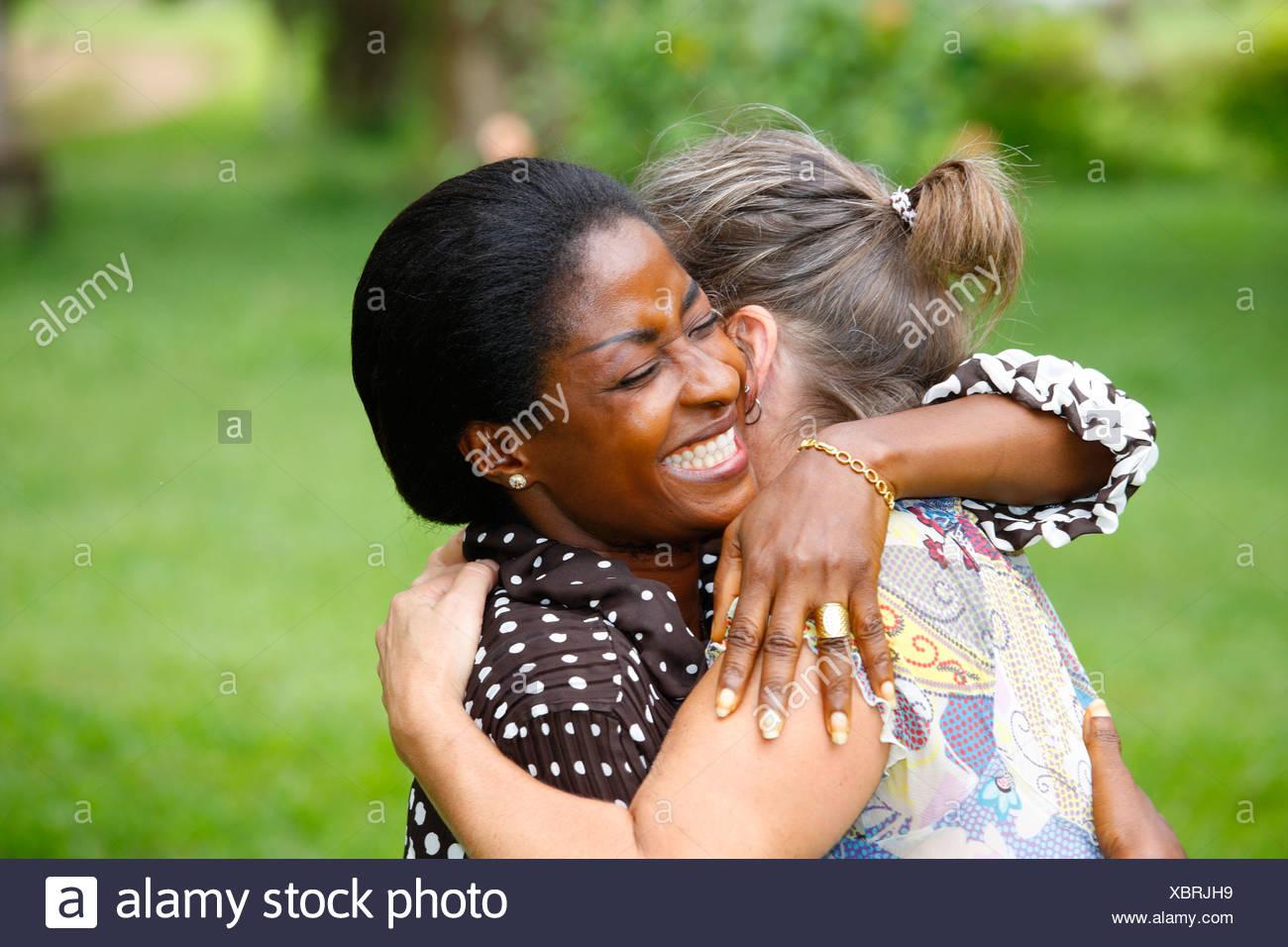 Women, light-skinned and dark-skinned, embracing, Kumba, Cameroon, Africa - Stock Image