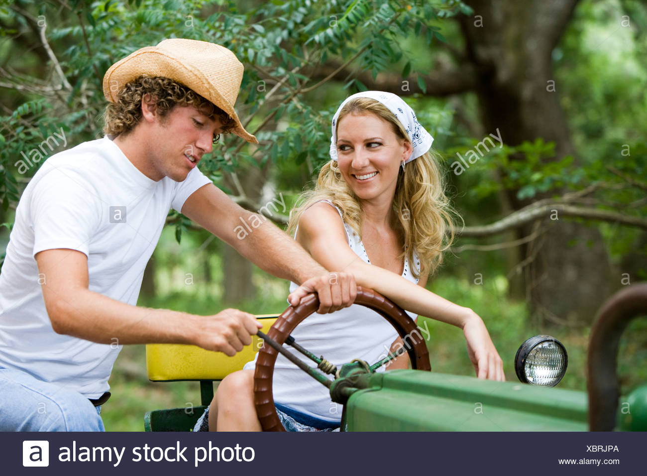 Pretty young woman on tractor with man in cowboy hat - Stock Image