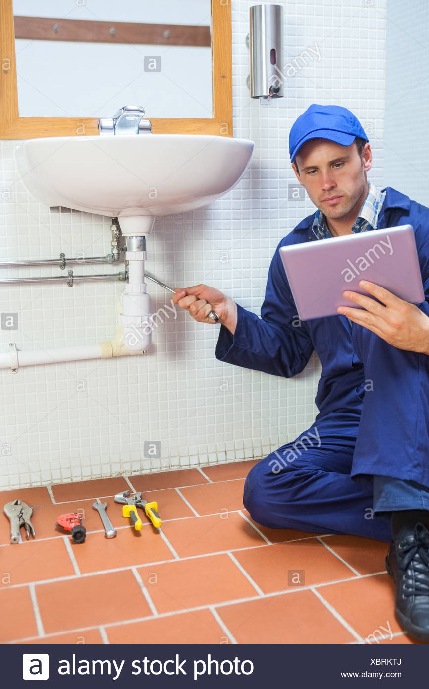 Focused plumber consulting tablet - Stock Image