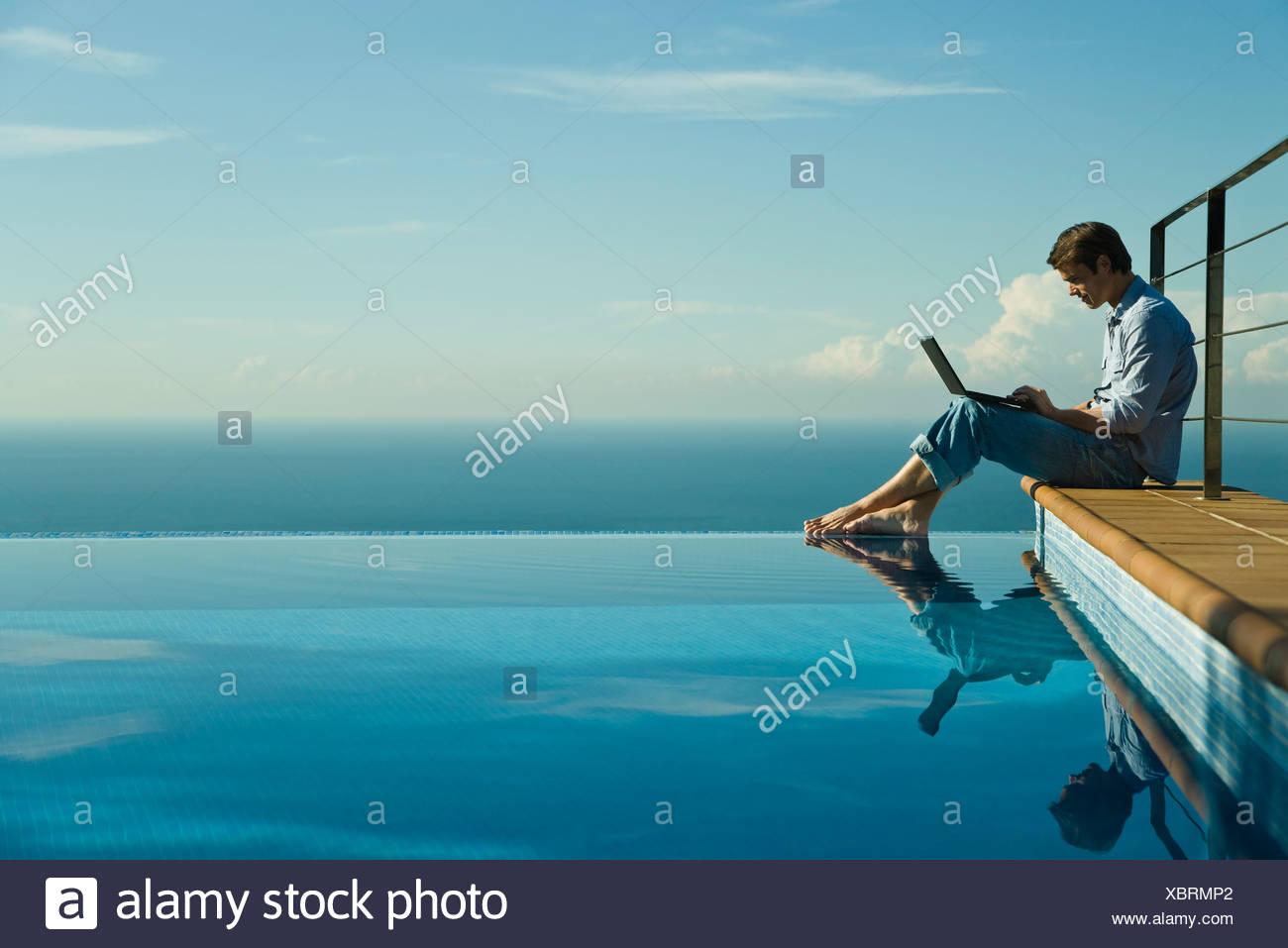 Man sitting beside infinity pool, using laptop computer - Stock Image