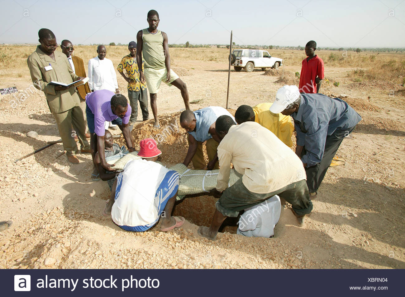 Body of a woman who died of HIV/AIDS being lowered into a grave during her funeral, Garoua, Cameroon, Africa - Stock Image